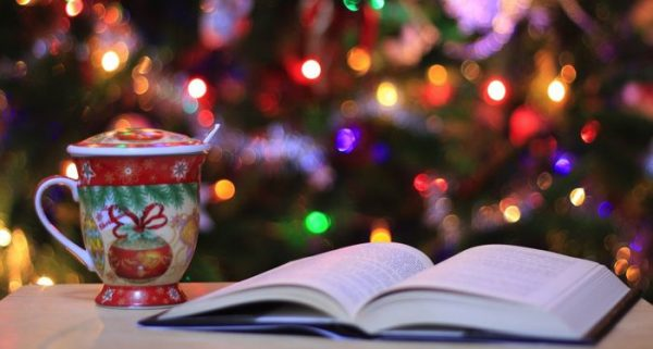 Photo of a book and holiday mug with a Christmas tree in the background