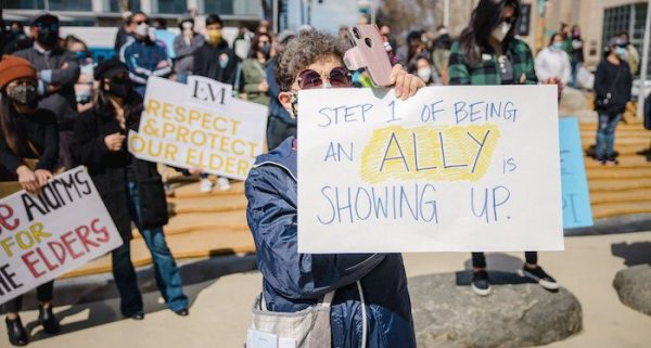 A photo of a sign at a protest reading Step 1 of being an ally is showing up